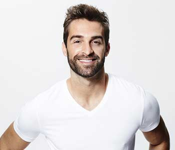 Handsome looking man smilling on a white background